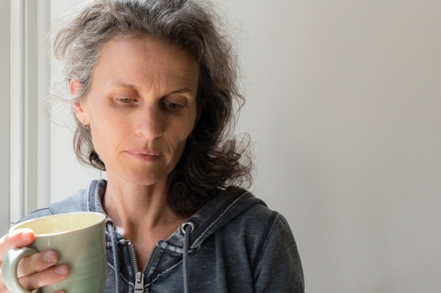 Sad middle-aged woman holding coffee cup