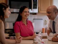 family sitting in kitchen talking
