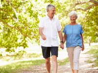 Older man and woman walking in park