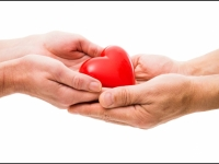 Person giving a heart figure to another person